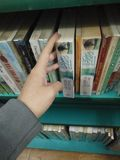 Libri del ritrovamento nella biblioteca Immagine Stock