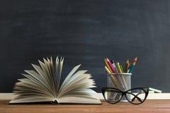 Libri dell'insegnante di vetro e un supporto con le matite sulla tavola, sui precedenti di una lavagna con gesso Il concetto del  Fotografie Stock Libere da Diritti