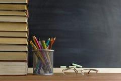 Libri dell'insegnante di vetro e un supporto con le matite sulla tavola, sui precedenti di una lavagna con gesso Il concetto del  Fotografia Stock Libera da Diritti
