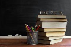 Libri dell'insegnante di vetro e un supporto con le matite sulla tavola, sui precedenti di una lavagna con gesso Il concetto del  Fotografie Stock