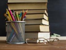 Libri dell'insegnante di vetro e un supporto con le matite sulla tavola, sui precedenti di una lavagna con gesso Il concetto del  Immagini Stock