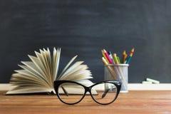 Libri dell'insegnante di vetro e un supporto con le matite sulla tavola, sui precedenti di una lavagna con gesso Il concetto del  Immagini Stock Libere da Diritti
