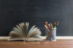Libri dell'insegnante di vetro e un supporto con le matite sulla tavola, sui precedenti di una lavagna con gesso Il concetto del  Immagine Stock