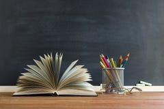 Libri dell'insegnante di vetro e un supporto con le matite sulla tavola, sui precedenti di una lavagna con gesso Il concetto del  Fotografia Stock