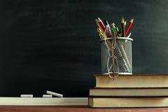Libri dell'insegnante e un supporto con le matite sulla tavola, sui precedenti di una lavagna con gesso Il concetto del ` s d del Immagini Stock