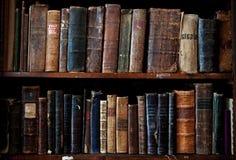 Libri dell'oggetto d'antiquariato sullo scaffale per libri Immagine Stock