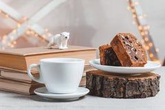 Libri della composizione, orso polare, dolce di cioccolato e tazza di caffè su fondo leggero fotografia stock libera da diritti