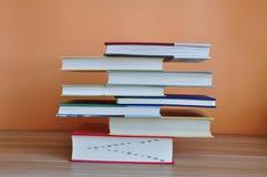 Libri della libro con copertina rigida sulla tavola di legno con fondo giallo fotografia stock libera da diritti