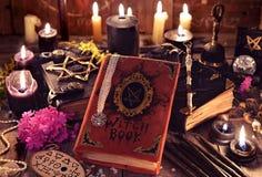 Libri della strega, candele nere con gli oggetti magici e mistici sulle plance Fotografia Stock Libera da Diritti
