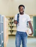 Libri di With Backpack And dello studente in biblioteca Fotografia Stock