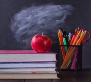 Libri di banco con la mela sullo scrittorio Fotografia Stock Libera da Diritti