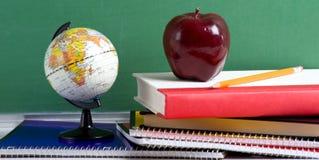 Libri di banco un Apple rosso e un globo Immagini Stock Libere da Diritti