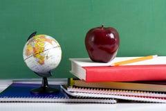Libri di banco un Apple rosso e un globo immagini stock