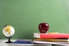 Libri di banco un Apple rosso e un globo Fotografia Stock