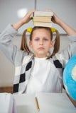 Libri di equilibratura svegli dell'allievo sulla testa in un'aula Fotografia Stock Libera da Diritti
