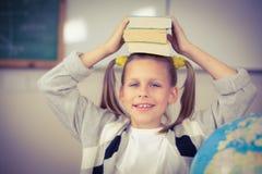 Libri di equilibratura svegli dell'allievo sulla testa in un'aula Immagine Stock Libera da Diritti