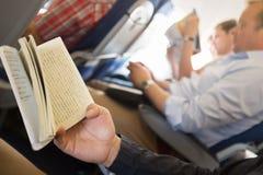 Libri di lettura in aeroplano Fotografia Stock