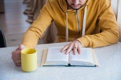 Libri di lettura alla tavola con una tazza di tè Fotografia Stock Libera da Diritti