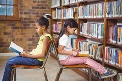 Libri di lettura degli allievi nella biblioteca Immagine Stock