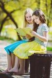 Libri di lettura dei bambini al parco Ragazze che si siedono contro gli alberi e lago all'aperto Immagine Stock