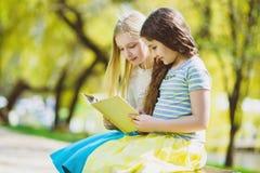 Libri di lettura dei bambini al parco Ragazze che si siedono contro gli alberi e lago all'aperto Immagini Stock