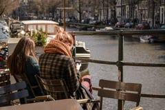 Libri di lettura dei giovani in un café all'aperto lungo un canale a Amsterdam Paesi Bassi Marzo 2015 fotografia stock libera da diritti