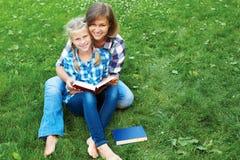 Libri di lettura del bambino e del genitore insieme nel parco fotografia stock