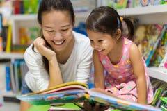 Libri di lettura del bambino e del genitore insieme nella biblioteca fotografia stock