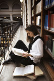 Libri di lettura dell'allievo allo scaffale per libri. Fotografia Stock