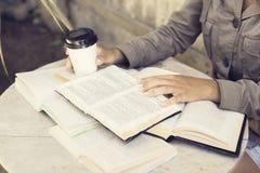 Libri di lettura della ragazza con la tazza di caffè Fotografie Stock
