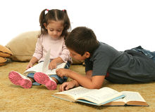 Libri di lettura della sorella e del fratello sul pavimento immagine stock libera da diritti