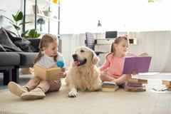 libri di lettura delle sorelline con il cane di golden retriever vicino immagini stock