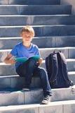Libri di lettura dello scolaro Bambino che fa compito all'aperto Di nuovo al concetto del banco Fotografia Stock