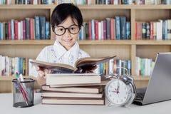 Libri di lettura dello studente di asilo in biblioteca Immagini Stock