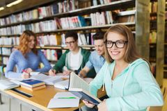 Libri di lettura felici degli studenti in biblioteca fotografie stock