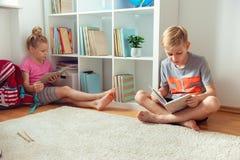 Libri di lettura felici dei bambini sul pavimento alla biblioteca di scuola immagini stock