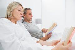 Libri di lettura rilassati delle coppie a letto Immagine Stock Libera da Diritti