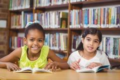 Libri di lettura sorridenti degli allievi nella biblioteca Fotografia Stock Libera da Diritti