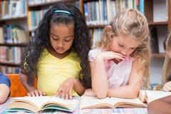 Libri di lettura svegli degli allievi in biblioteca Fotografia Stock Libera da Diritti