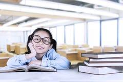 Libri di lettura svegli della scolara in aula Fotografia Stock