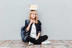 Libri di pensiero della tenuta dello studente della giovane donna sulla testa Fotografie Stock