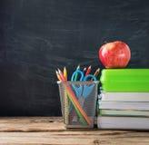 Libri di scuola con cancelleria e la mela sul fondo della lavagna fotografia stock