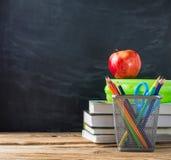 Libri di scuola con cancelleria e la mela sul fondo della lavagna fotografia stock libera da diritti