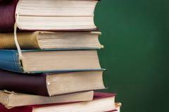 Libri di scuola sopra la lavagna immagine stock