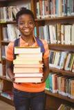 Libri di trasporto del ragazzino sveglio in biblioteca Fotografia Stock Libera da Diritti