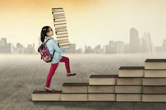 Libri di trasporto della ragazza e camminare verso l'alto Immagine Stock