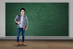 Libri di trasporto dello studente maschio nell'aula Fotografie Stock