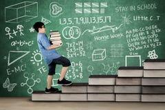 Libri di trasporto dello studente primario sulla scala Fotografie Stock Libere da Diritti