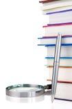 Libri e lente d'ingrandimento isolati su bianco Immagine Stock