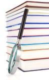 Libri e lente d'ingrandimento su bianco Immagine Stock